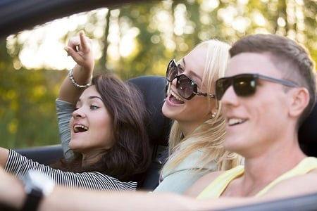 Group of three carefree cheerful friends on vacations, traveling in convertible on summer day, having fun together